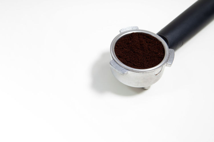 Portafilter filled with ground coffee on a white background Arabica Basket Cafe Caffeine Close-up Coffee Day Drink Espresso Filter Food And Drink Freshness Grounded Indoors  No People Portafilter Refreshment White Background