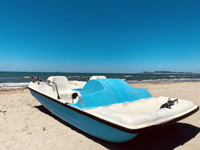 Panoramic view of pedal boat on the beach against clear blue sky