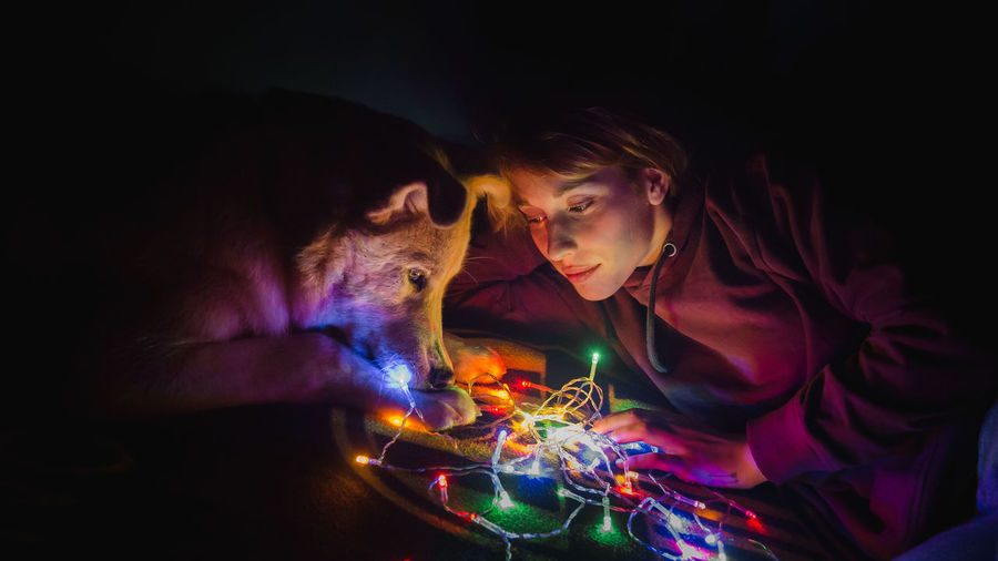 Woman looking at christmas lights with dog