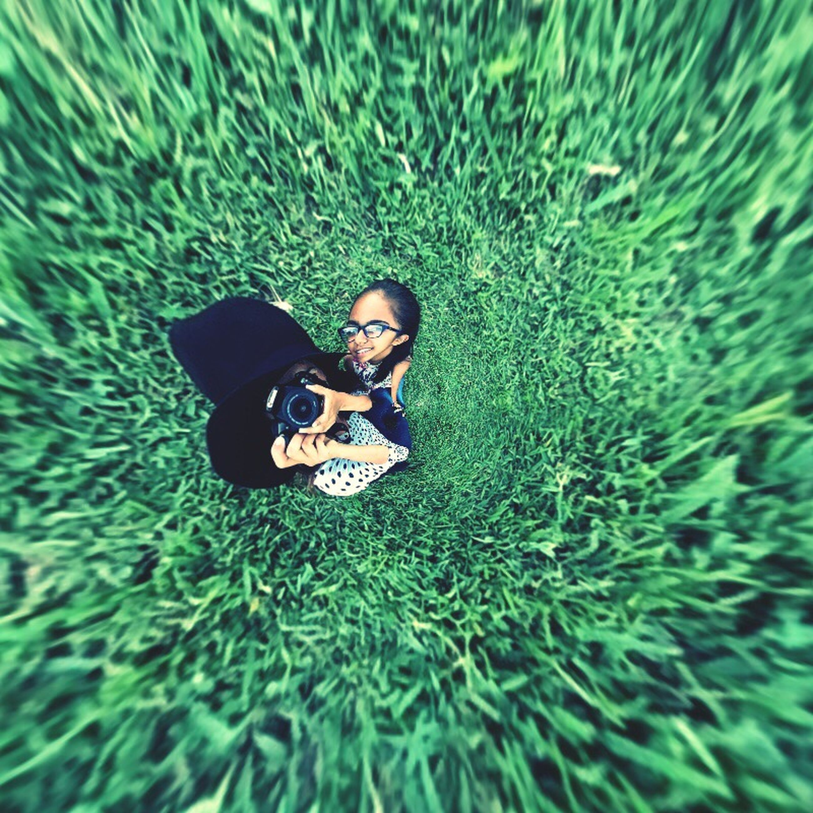 lifestyles, leisure activity, high angle view, shoe, grass, sunglasses, photography themes, green color, technology, field, casual clothing, photographing, men, toy, day, front view, camera - photographic equipment, childhood