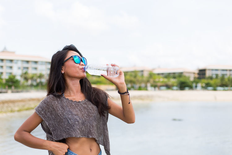 Young adult girl drinking water. Adult Bali Indonesia Beach Beautiful Woman Day Hydration One Person One Young Woman Only Only Women Outdoors People Sand Sea Standing Summer Summertime Sunglasses Thirsty  Vacations Water Water Bottle  Young Adult Young Women