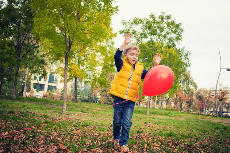 Balloon One Person Nature Casual Clothing Outdoors Boys Kid Childhood Child Children Only Playing Playful Helium Balloon Red Red Balloon Innocence Park - Man Made Space Autumn People Caucasian Blond Hair Carefree Cute Happiness Leisure Activity Lifestyles Day Fun Full Length