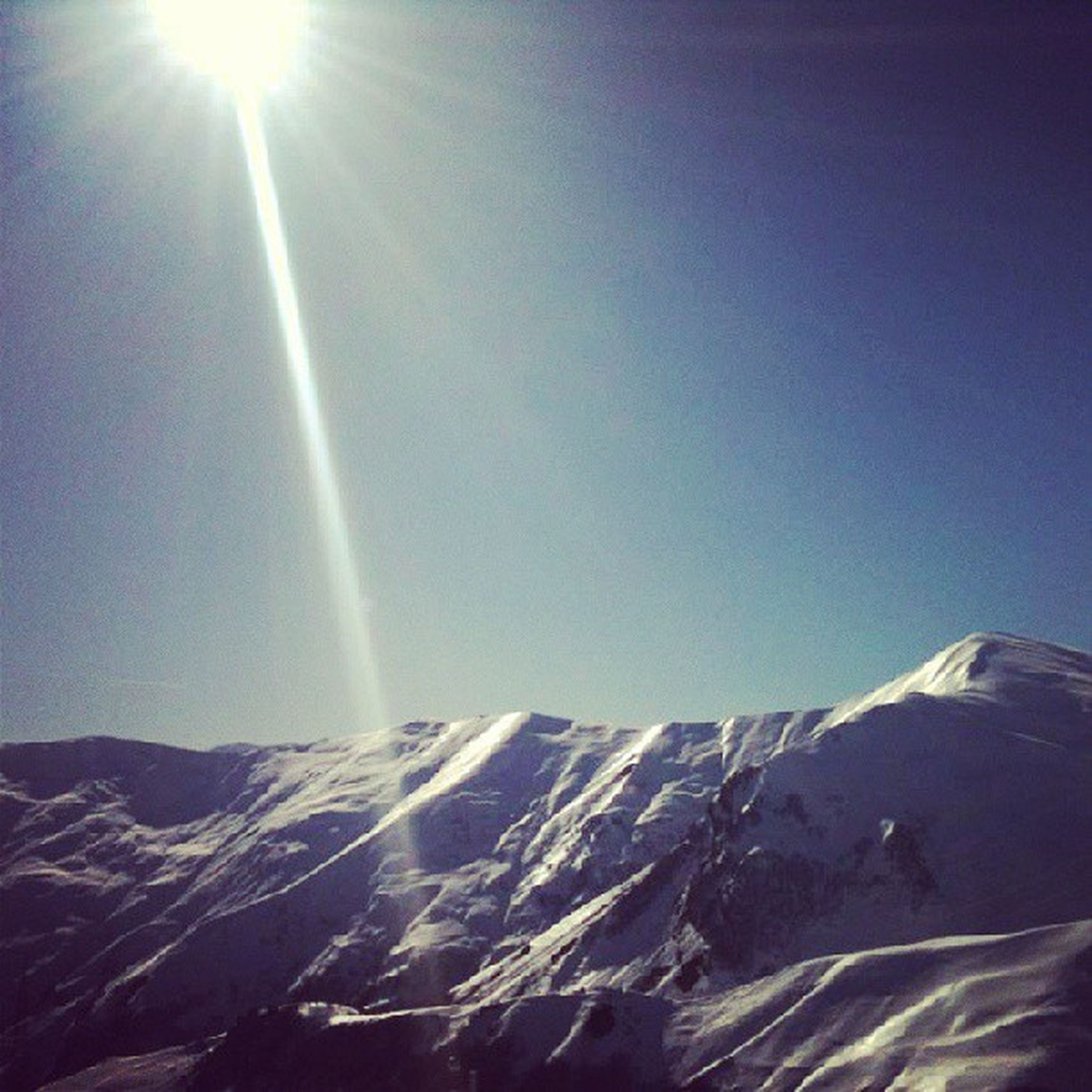 sun, sunbeam, mountain, tranquility, scenics, tranquil scene, sunlight, lens flare, snow, beauty in nature, clear sky, cold temperature, winter, nature, mountain range, landscape, blue, low angle view, snowcapped mountain, copy space