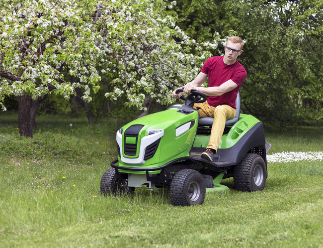 Young man, gardener driving ride on mower. Mowing grass in yard, tractor. Gardening. Backyard Blooming Countryside Garden Gardener Gardening Grass Grass Cutter Grass Cutting. Home Lawn Lawn Mower Lawn Mowing Lawnmower Mower Mowing Mowing Tractor Nature One Person Outdoors Riding Mower Spring Tractor Tree Yard