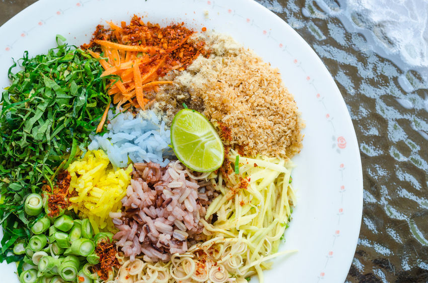 "Thai Cuisine ""Khao Yam in Southern Style"". A kind of rice salad with plenty of vegetable dressing with special salad dressing called ""Budu"" Carrot Chili  Citrusfruit  Close-up Coconut Cucumber Dried Shrimp Food Freshness Green Beans Green Papaya Healthy Eating Herb High Angle View Kaffir Lime Leaves Khao Yam Lemongrass Lime No People Ready-to-eat Rice Salad Southern Thailand Spicy Thai Food Winged Bean"