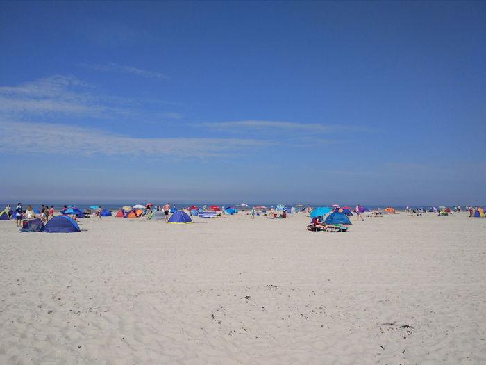 People at sandy beach against sky