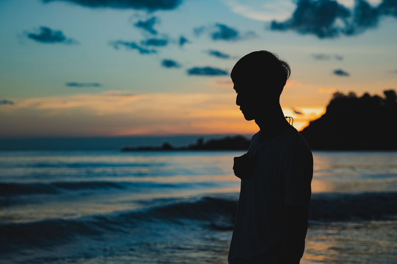Silhouette man looking at sea against sunset sky