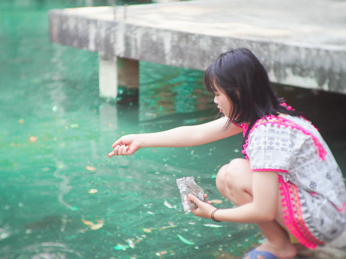 Woman spilling food in pond