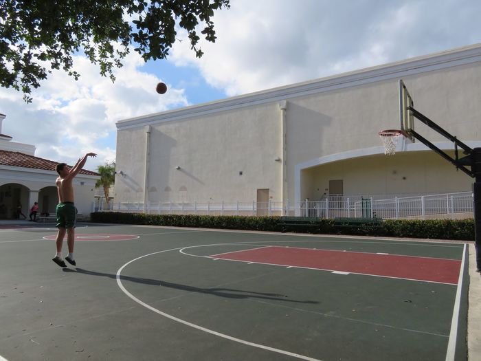 Court Sport Built Structure Ball Architecture Basketball - Sport Building Exterior Basketball Hoop Playing Sky Real People Cloud - Sky Mid-air Tennis Taking A Shot - Sport Day Outdoors Leisure Games Tennis Ball One Person