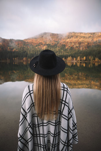 Rear view of woman in hat against lake