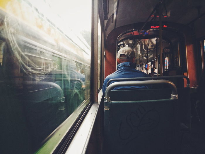 Rear view of man sitting in passenger train