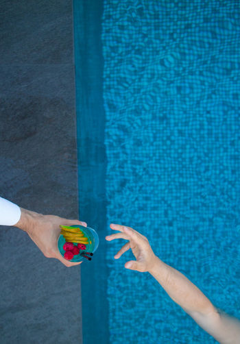 a hand grabbing a cocktail from the swimming pool Cocktail Blue Close-up Day Drink Drinking Drinking Glass Fruit High Angle View Holding Human Body Part Human Hand Leisure Activity Lifestyles Multi Colored One Person Outdoors People Real People Swimming Pool Water