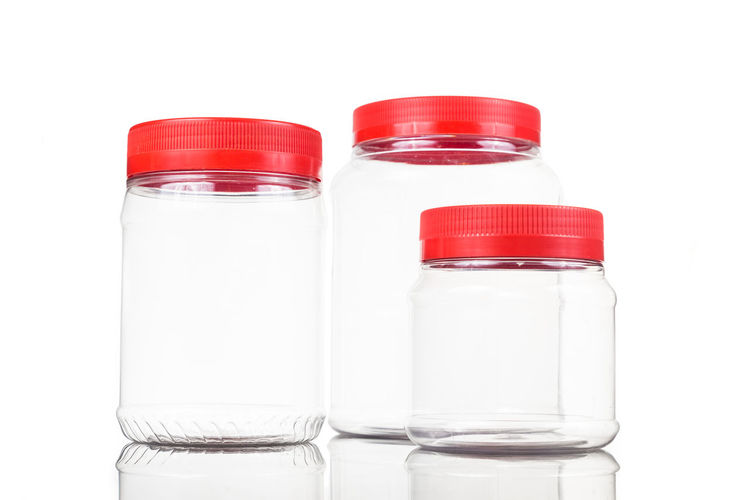 Plastic jar bottle with red cover lid against white background Bottle Close-up Container Cover Cut Out Food And Drink Glass - Material Group Of Objects Healthcare And Medicine Indoors  Lid No People Plastic Polyurethane Red Color Side By Side Still Life Studio Shot Transparent White Background White Color