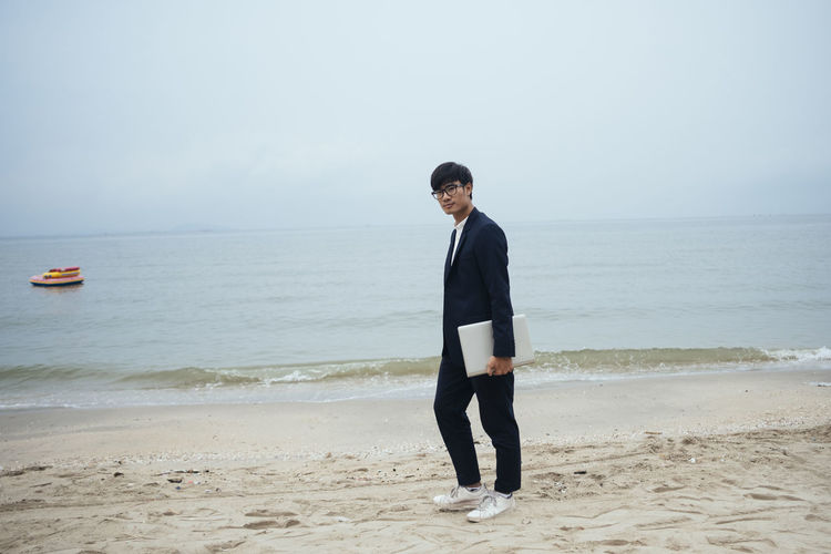 Young man standing on beach against sky