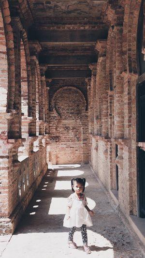 Girl standing on corridor of historical building