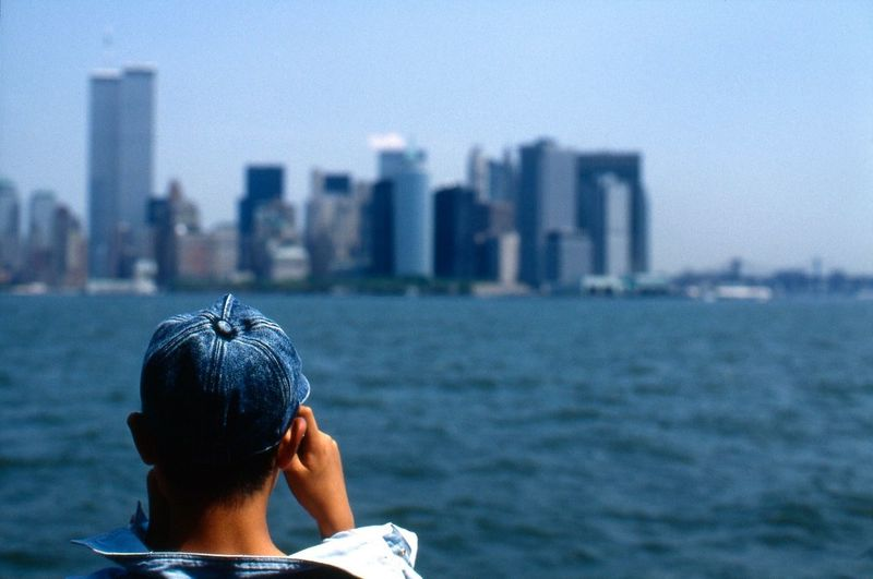 Rear view of man looking at east river by cityscape against sky