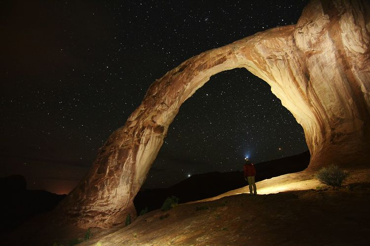 Man standing by illuminated corona arch against star field
