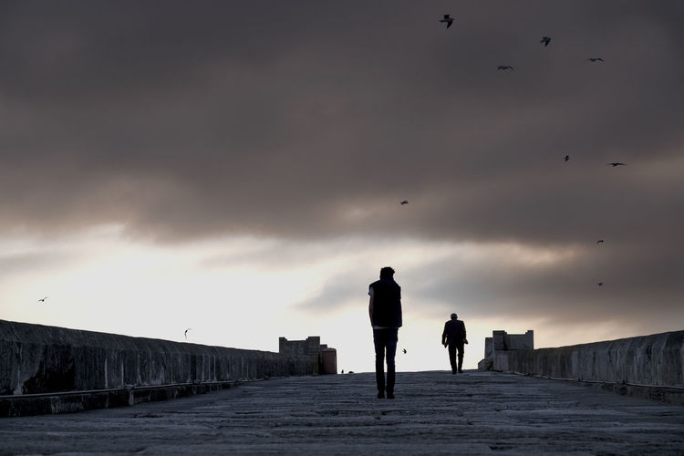Silhouette people walking against cloudy sky