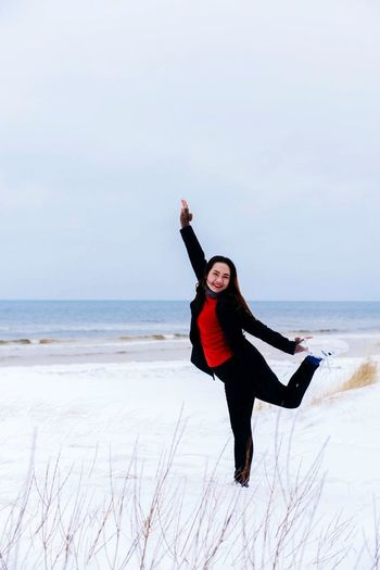 Portrait of woman standing on one leg at beach against sky during winter
