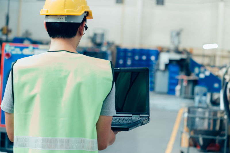 Rear view of man working in laptop