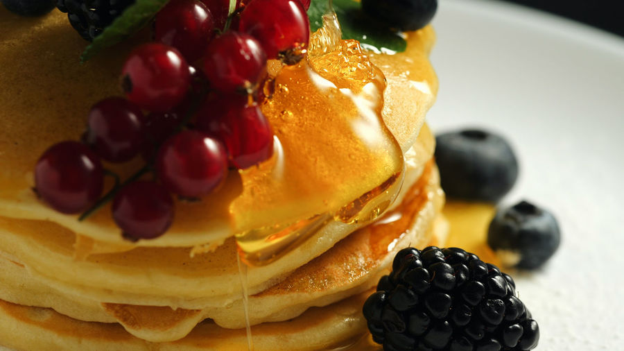 Stack of homemade pancakes or crepes decorated on top with forest berries - red currant, blackberry and blueberry. Delicious, healthy classic american breakfast. Side view. Close-up Food Food And Drink Fruit Freshness Sweet Food Sweet Dessert Healthy Eating Indulgence Close-up Berry Fruit Ready-to-eat Temptation Indoors  Still Life No People Plate Cake Blueberry Snack Red Currant Pancakes Pancake Breakfast Berries