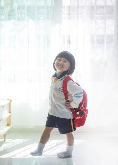 Full length of smiling girl standing against window