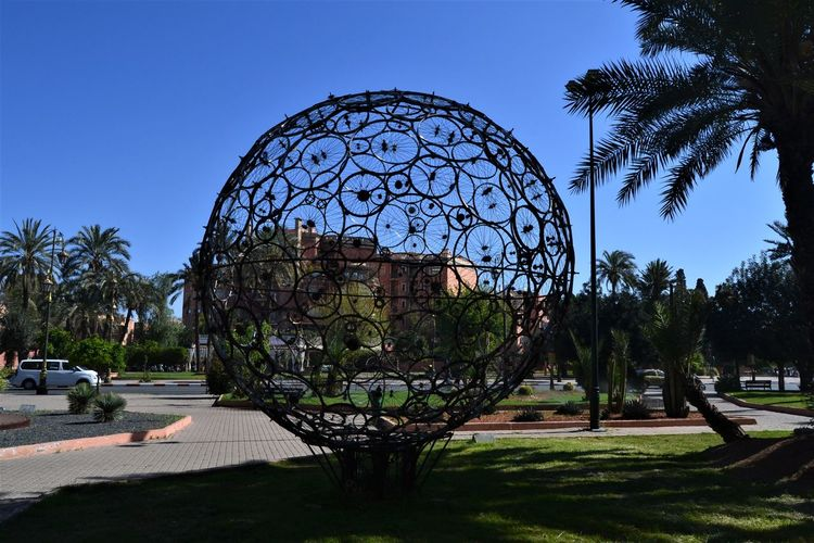 Bicycle wheel sculpture in a city park against a clear blue sky in Morocco. Tree Plant Sky Architecture Nature No People Clear Sky Day Built Structure Park Palm Tree Outdoors Art And Craft Building Exterior Growth Blue Sunlight Shadow Travel Destinations Tropical Climate Bicycle Wheel Sculpture Artistic Expression