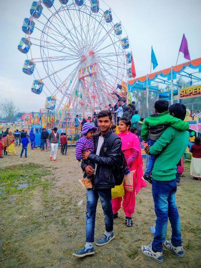 People in amusement park ride against sky