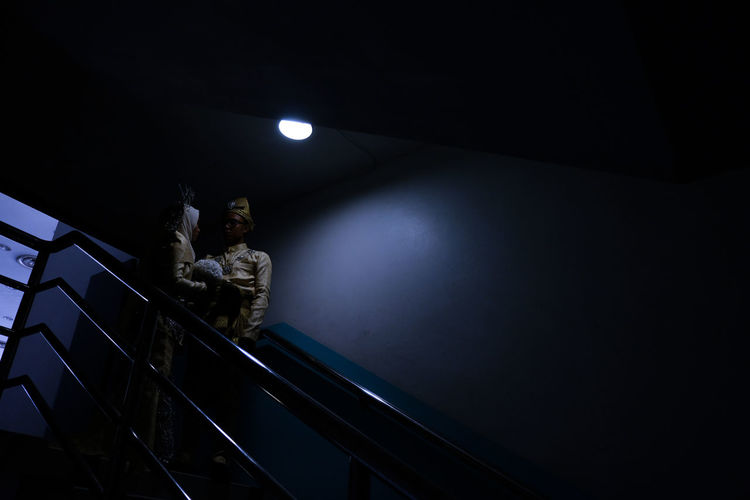 Low angle view of people on illuminated staircase