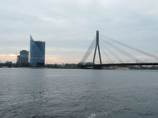 Architecture Bridge - Man Made Structure City Skyscraper Urban Skyline Downtown District Cityscape Built Structure Steel Sky Connection Modern Suspension Bridge Cloud - Sky Outdoors Building Exterior Travel Destinations Business Finance And Industry City Life River Riga