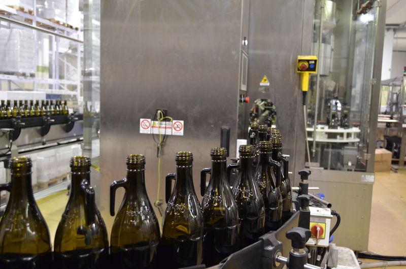 Glass of olive oil bottles on line in olive oil factory