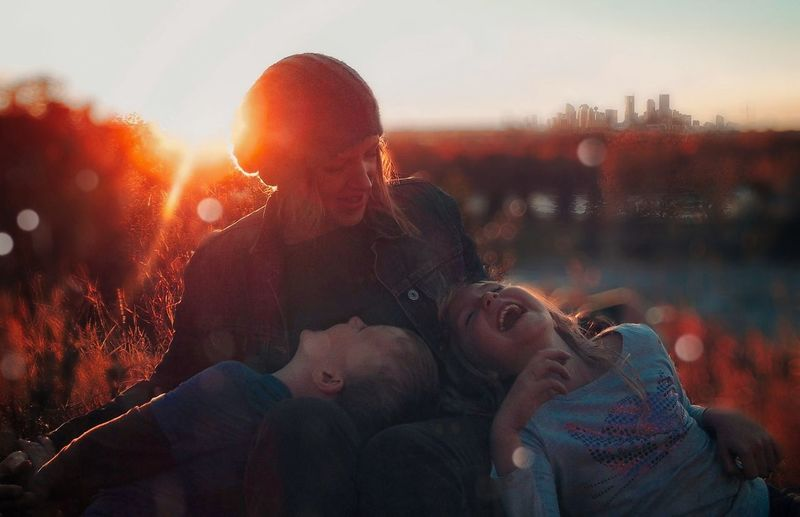 View of mother and children against sky during sunset