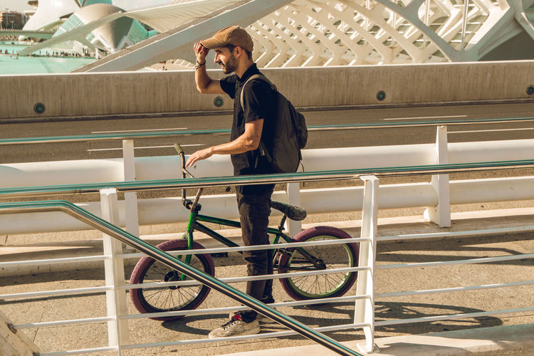 Side view of young man with bicycle on railing