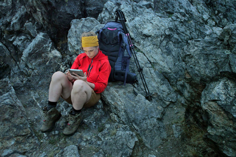 caucasian female hiker using portable tablet technology outdoors on a alpine hiking trail Alpine Backpacking Camping Expedition Freedom Hiking Tablet Travel Trekking Woman Youth Activity Adult Adventure Backpack Battery Climbing Connection Day Extreme Sports Female Full Length Headwear Helmet Hobby Holding Internet Leisure Activity Nature Navigation One Person Outdoors People Portable Information Device Rock Rock - Object Sitting Solid Sport Technology Trail Wireless Technology