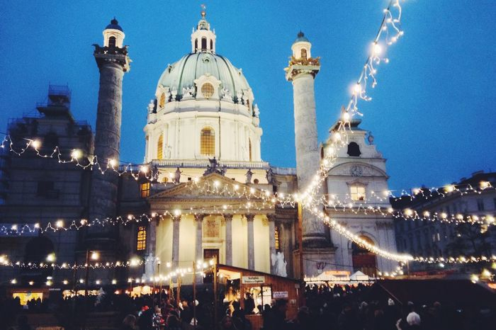 Karlskirche in Vienna, Austria Architecture Building Exterior Built Structure City Crowd Dome History Illuminated Large Group Of People Men Night Outdoors People Place Of Worship Real People Religion Sky Spirituality Travel Destinations