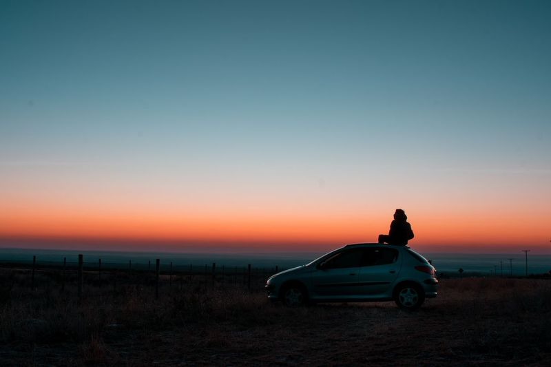 Silhouette car on land against sky during sunset