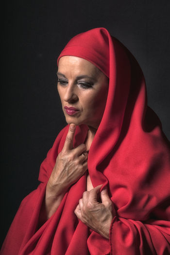 Thoughtful mature woman with red headscarf standing against black background