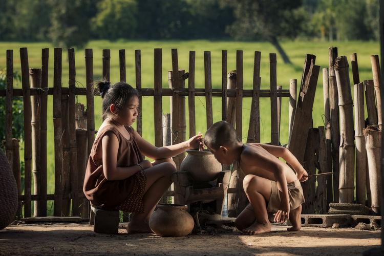 Siblings Preparing Food Against Fence