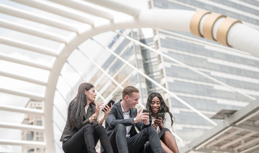 Smiling business colleagues using smart phone while sitting against buildings in city