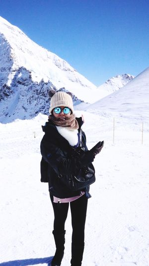 Full Length Of Woman Wearing Warm Clothing Standing On Snowcapped Mountain