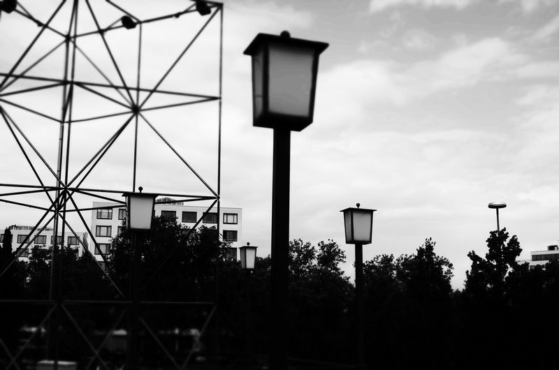Low angle view of street light at park against tees
