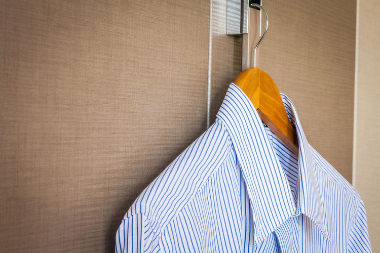 Cropped image of shirt hanging on cabinet