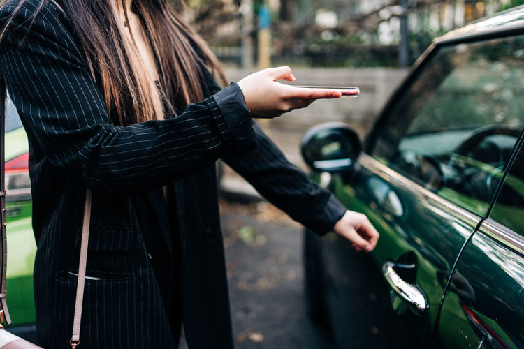 Midsection of woman using mobile phone in car
