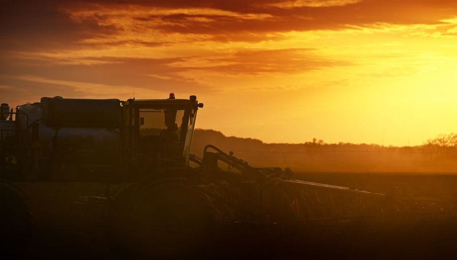 Agricultural machinery on field against sky during sunset