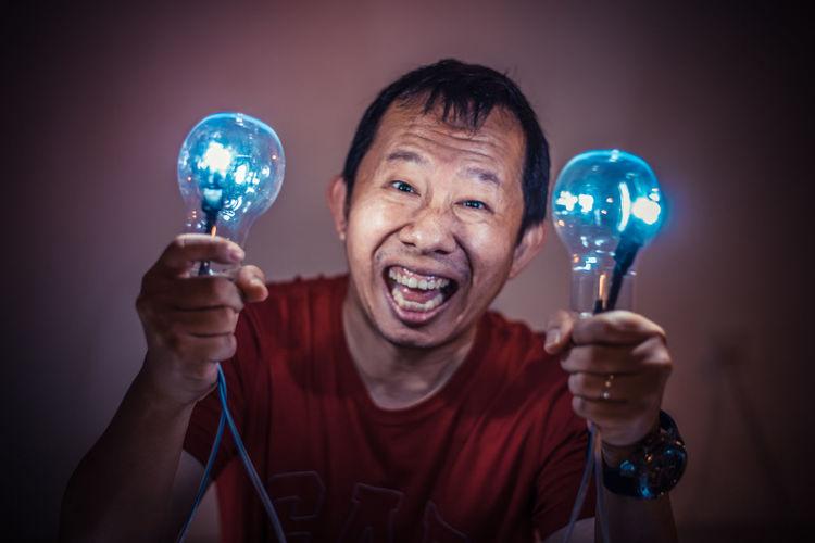 Portrait of man holding illuminated light bulbs