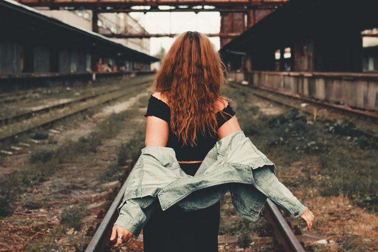 Rear view of woman standing on railroad track