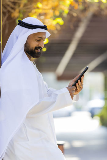 Side view of man in traditional clothing using mobile phone