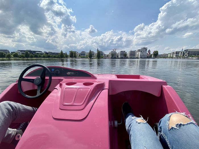 Low section of man on boat in lake against sky