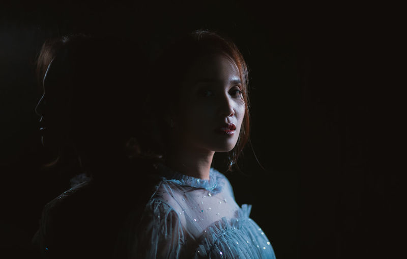 Portrait of a girl looking away over black background