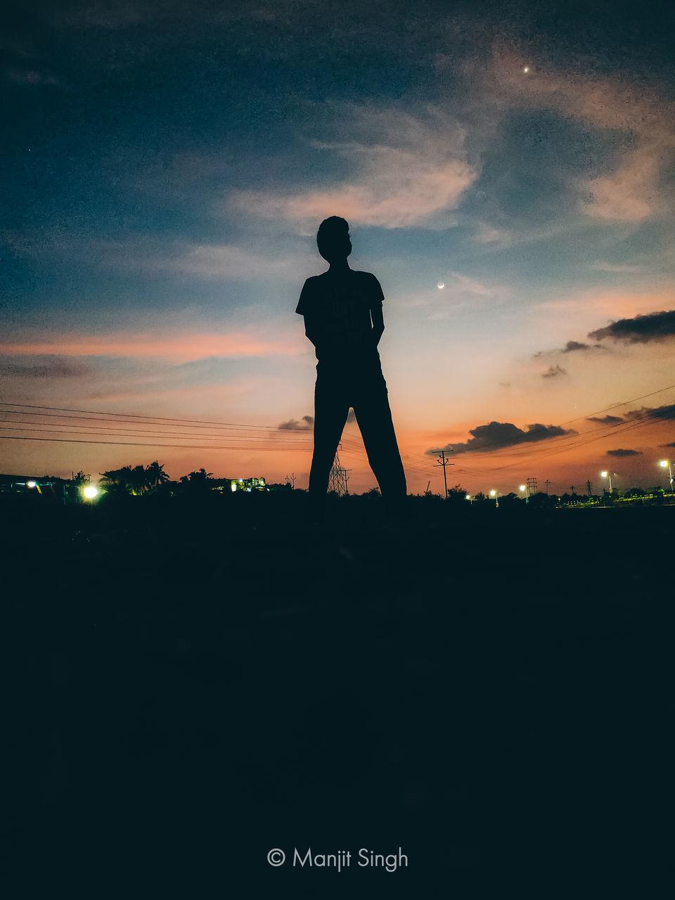SILHOUETTE MAN STANDING ON FIELD AGAINST ORANGE SKY